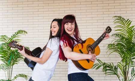 Side view of young women smiling and playing Spanish guitars while standing back to back against brick wall