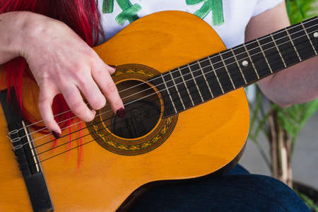 Crop female in t shirt with transgender symbol touching strings of acoustic guitar while playing song Foto de archivo