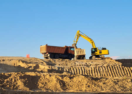 Digger working with two trucks at building site on sunny day. Excavator working in Valdebebas, Madrid. Foto de archivo