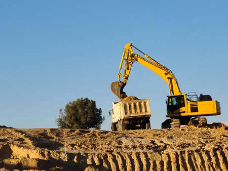 Excavator machine filling truck in construction site on sky background. Excavator working in Valdebebas, Madrid.
