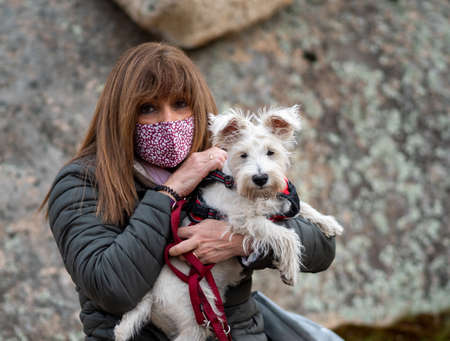 Adult woman with face mask holding white dog in a defocused stoned background outside. Foto de archivo