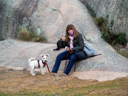 Adult woman sitting on a rock with her thumb up and her dog next to her, both looking at the camera. Woman wearing face mask and holding by leash her white dog.