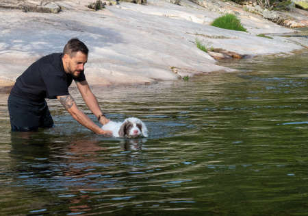 Dog handler teaching puppy to swim in lagoon. White puppy learning to swim in a lake.