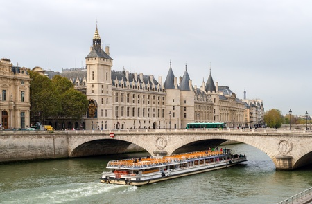 seine: View of Conciergerie, Pont au Change and excursion boat in Paris, France
