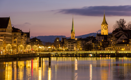 grossmunster cathedral: Zurich on banks of Limmat river at winter evening