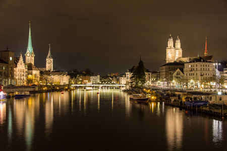 Zurich on banks of Limmat river at winter evening photo