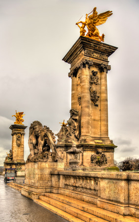 Sculptures at the entrance to the Pont Alexandre III in Paris photo
