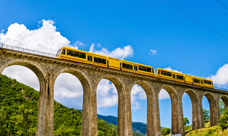 railway transports: The Yellow Train (Train Jaune) on Sejourne bridge - France, Pyrenees-Orientales
