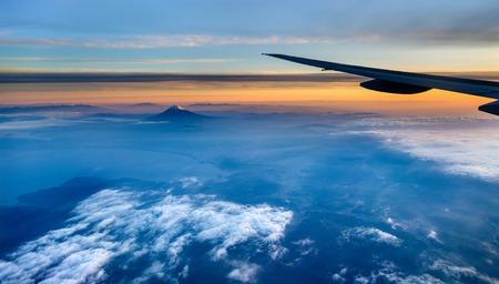 Flying above Japan: view of Mount Fuji through airplane window.