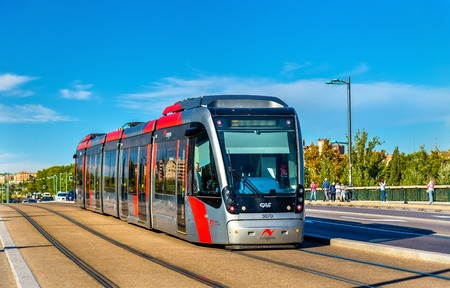 Zaragoza, Spain - October 8, 2016: Tram CAF Urbos 3 on Santiago Bridge. The tram system of Zaragoza consists of a single line with 11 stations