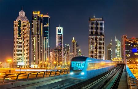 배경 - 두바이, 아랍 에미리트 고층 빌딩이있는자가 운전 지하철 열차 스톡 콘텐츠