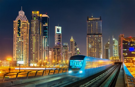 Self-driving metro train with skyscrapers in the background - Dubai, UAE Stock Photo