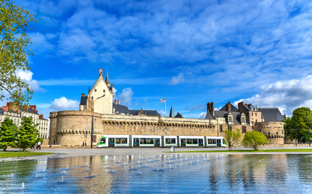 Castle of the Dukes of Brittany, a City tram and the Water Mirror fountain in Nantes - France, Pays de la Loire Foto de archivo