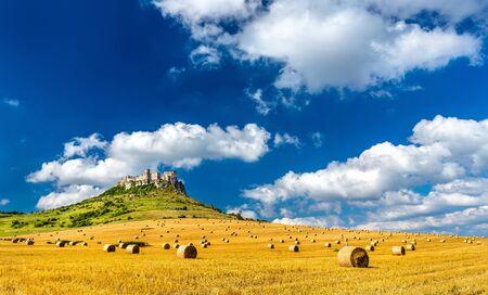 Vista de Spissky hrad y un campo con fardos redondos en Eslovaquia, Europa Central Foto de archivo - 88561570