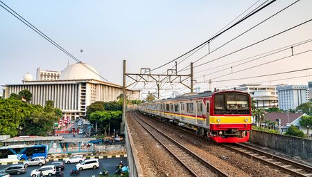 Commuter train near Istiqlal Mosque in Jakarta, the capital of Indonesia Zdjęcie Seryjne