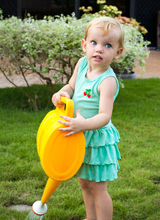 curious baby girl with the watering can photo