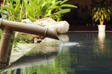 beauty fountain: water falling down from bamboo pipe. Stock Photo