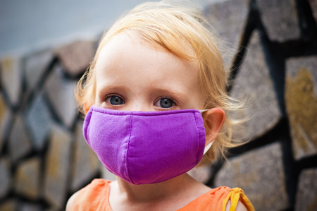 Cute little girl in bright face mask.