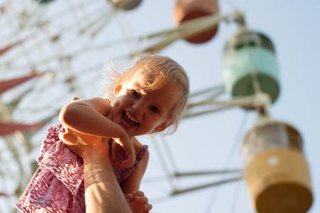 ni�os jugando en el parque: chica de pap� manos cerca de la noria.