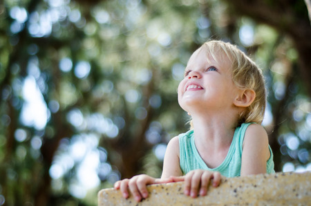 cute blonde: Adorable toddler girl looking up above the camera shallow focus.