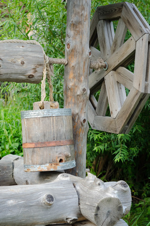 draw well: Old draw well with wooden bucket. Stock Photo