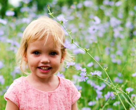 beauty eyes: Cute little girl in a pink dress smiling in park looks at camera. Stock Photo