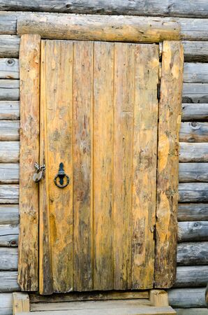 balk: Loghouse wooden door with a padlock.