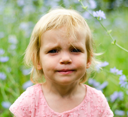 grumpy: Little girl with a cute grumpy face expression. Stock Photo