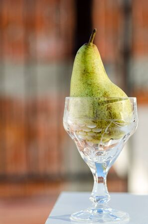 hight: Green pear in hight wineglass.