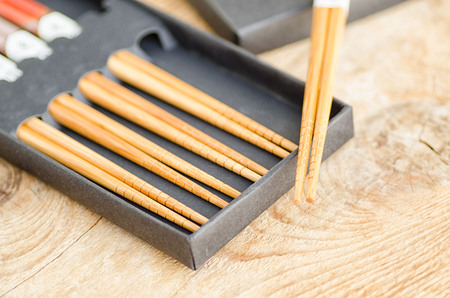 chinese bamboo: Chinese bamboo chopsticks in black box on wooden background.