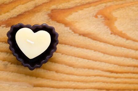 st valentin: Heart shaped candle on wooden background.