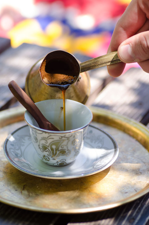 Pouring turkish coffee from traditional metal pot.