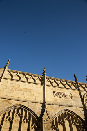 View of Bradford Cathedral logo and sign on Forster Square steps entrance against blue sky. September, 2013 Editorial