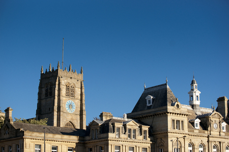 View of Bradford Cathedral from Forster Square showing the main tower against blue sky.