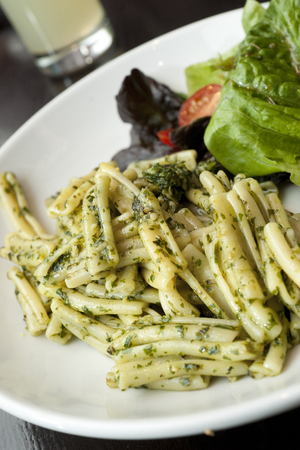 Pasta Dish with Green Pesto and Salad on a White Plate