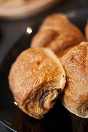 A stack of Pain au Chocolat on a Cafe style counter.