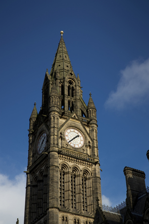 Manchester Town Hall in Albert Square against a blue sky.