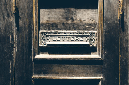 Old italian letter box on a vintage rustic wooden door Stock Photo