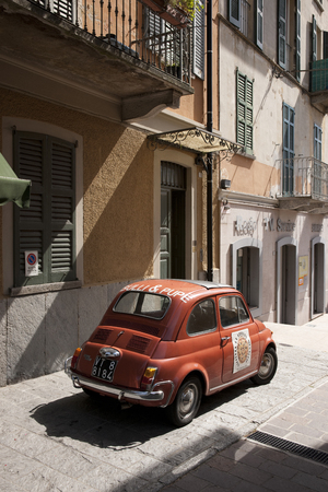 A classic red Fiat 500 car parked in a traditional Italian street near Lake Como, Lombardy, Italy - 29th August 2011