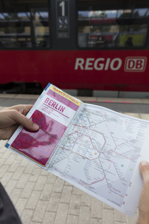 Potsdam, Berlin, Germany: 18th August 2018: Tourist looking at Marco Polo Guide and Public transport map