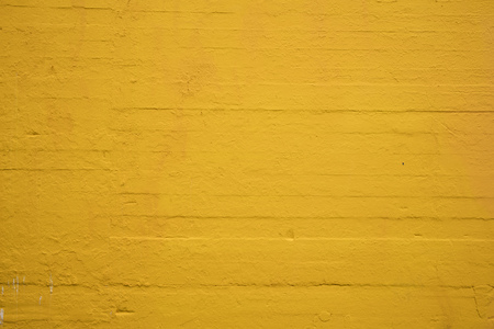 Textured concrete wall painted sunflower yellow Redactioneel