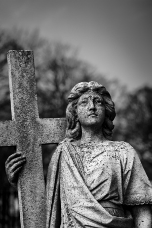Angel with Crucific Carving on a stone headstone in the grounds of Bridlington Priory, Bridlington, East Riding of West Yorkshire, UK - March 2014 Editorial