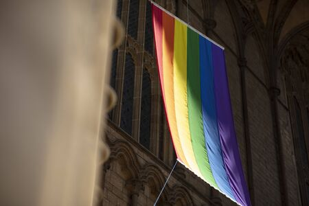 Peterborough, Cambridgeshire, United Kingdom, July 2019, A view of a Pride flag hanging from Peterborough Cathedral Editorial