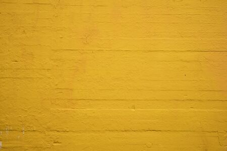 Textured concrete wall painted sunflower yellow Stock Photo