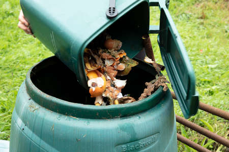 A woman emptying a home composting bin into an outdoor compost bin to reduce waste Stock Photo - 153767439