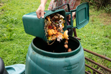 A woman emptying a home composting bin into an outdoor compost bin to reduce waste Stok Fotoğraf