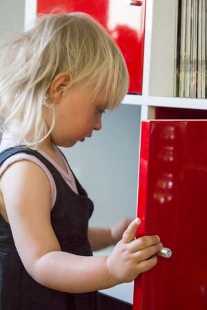 kiddy: Infant searching for chocolate in cupboard Stock Photo