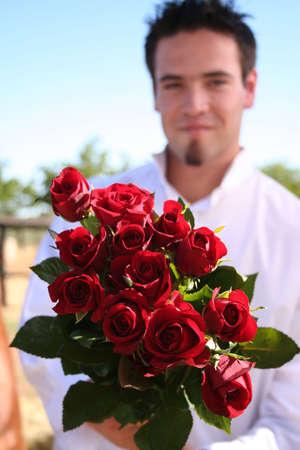 suitor: Giovane uomo regge un cespuglio di rose (Modello fuori fuoco)