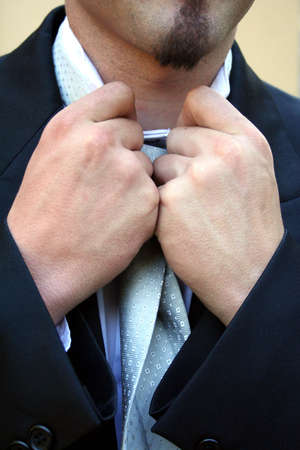 Young man doing a tie, creating a shape with his hands. Stock Photo - 952111