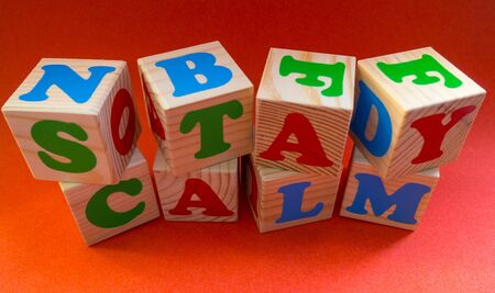Stay calm message made of wooden kids blocks on orange background. Motivation quote Stay calm for stay-at-home order mode Concepts: isolation, medical, virus